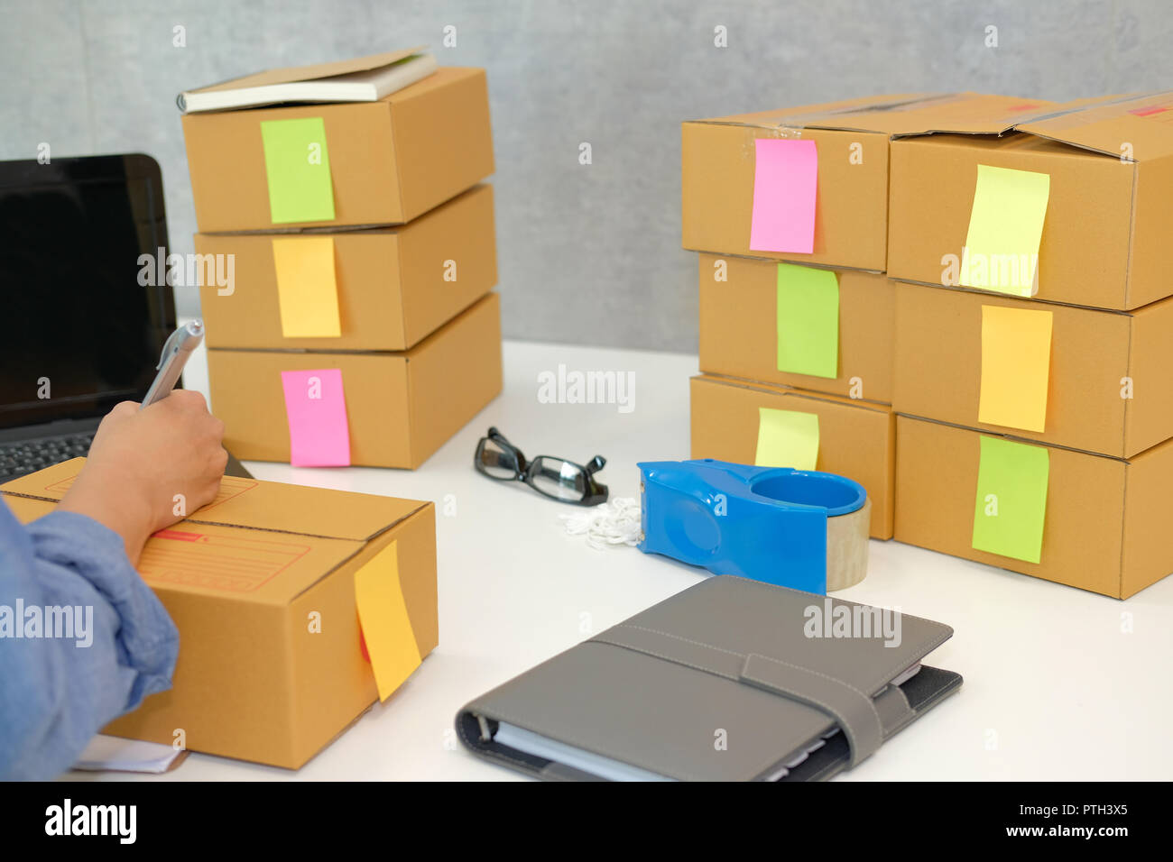 startup small business owner writing address on cardboard box at