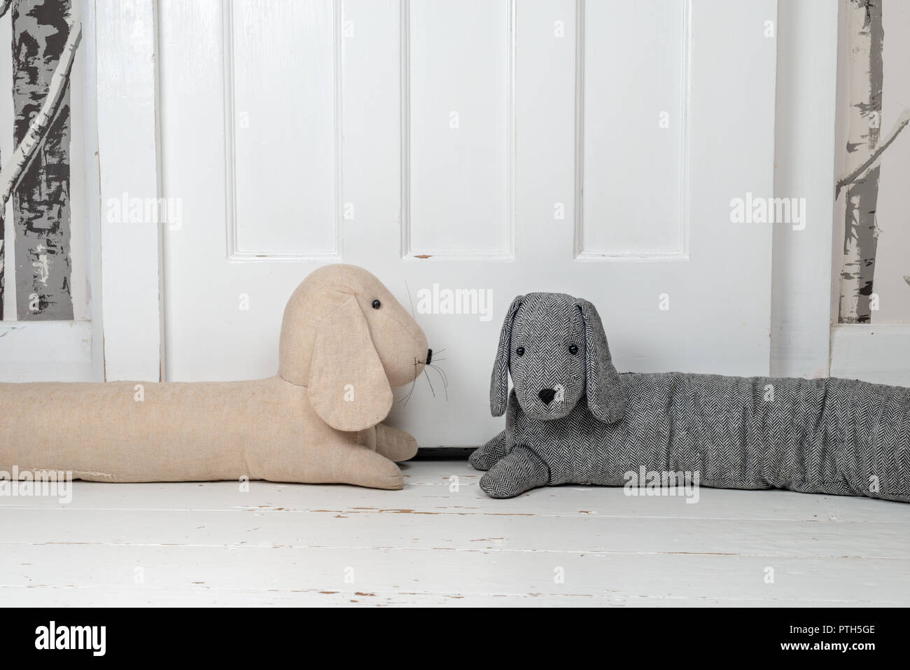 Two dog shaped draught excluders on a white painted wooden floor and in front of a door. - Stock Image