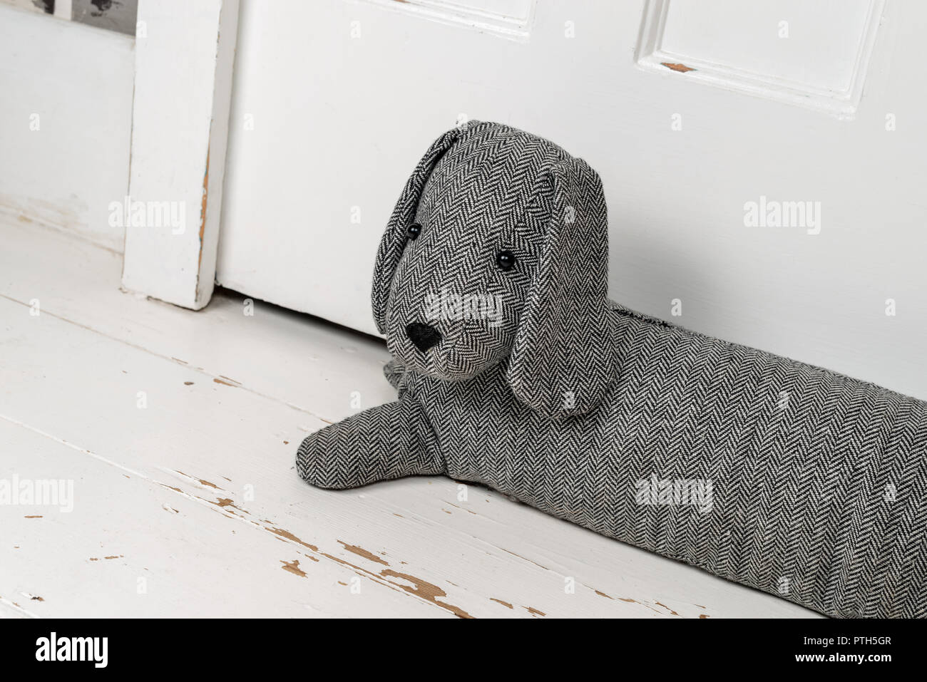 A dog shaped draught excluder on a white painted wooden flloor and in front of a door. - Stock Image
