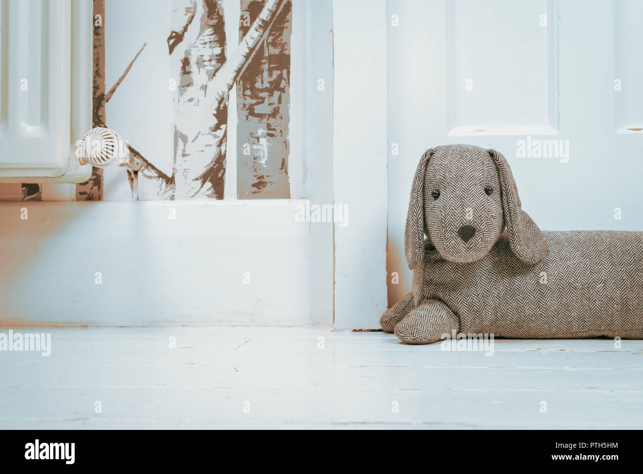 A dog shaped draught excluder next to a door and a radiator. - Stock Image