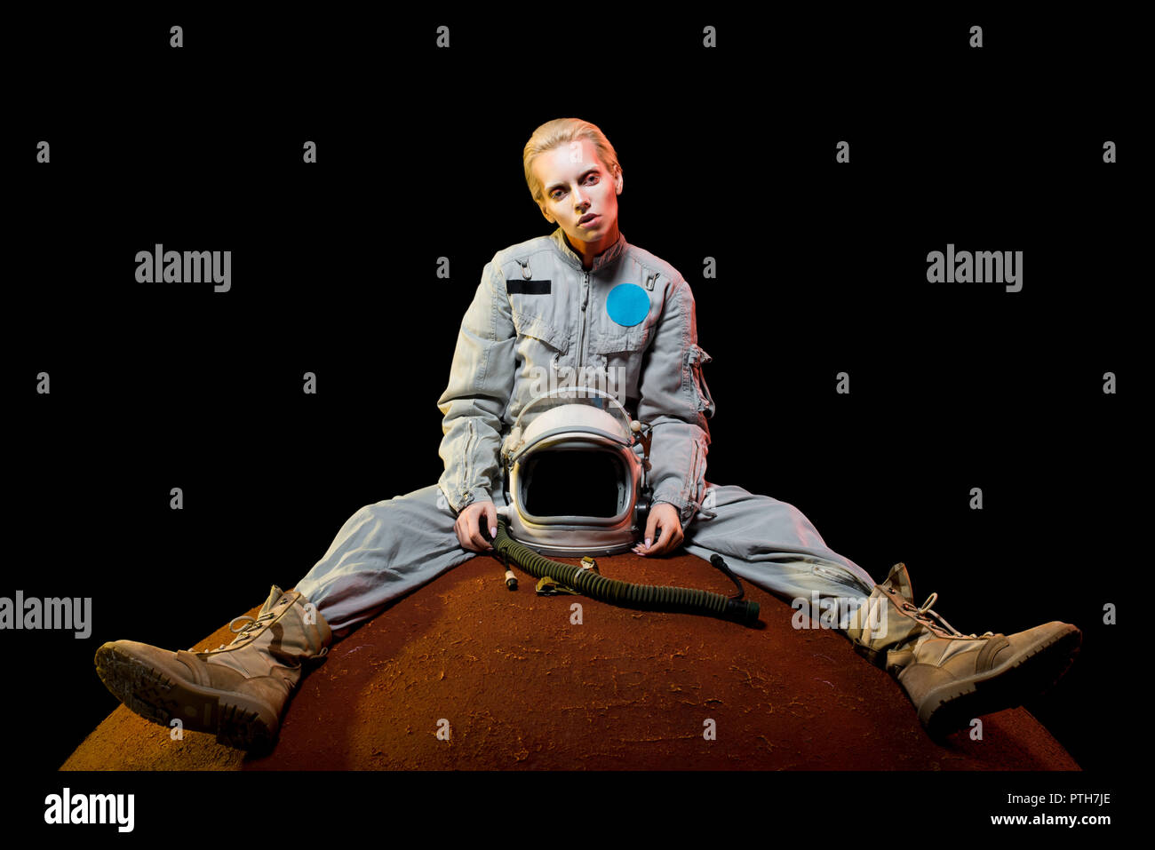 attractive spacewoman in spacesuit with helmet sitting on planet - Stock Image