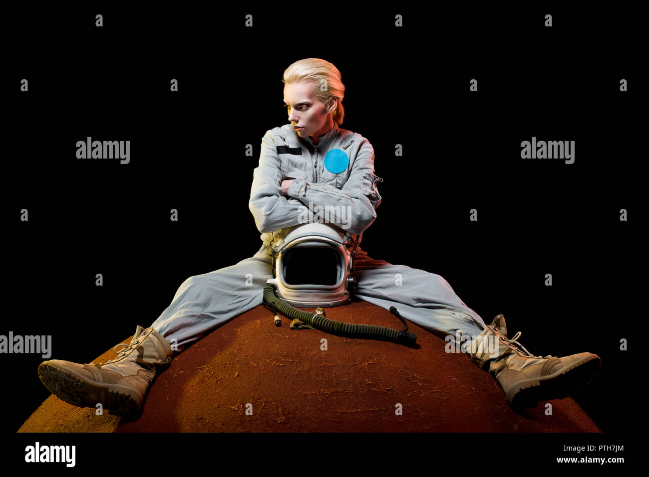beautiful astronaut in spacesuit with helmet sitting on planet - Stock Image