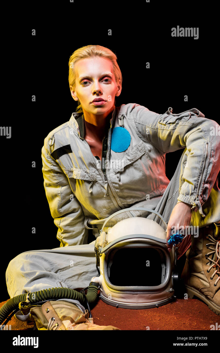 attractive astronaut in spacesuit with helmet sitting on planet - Stock Image
