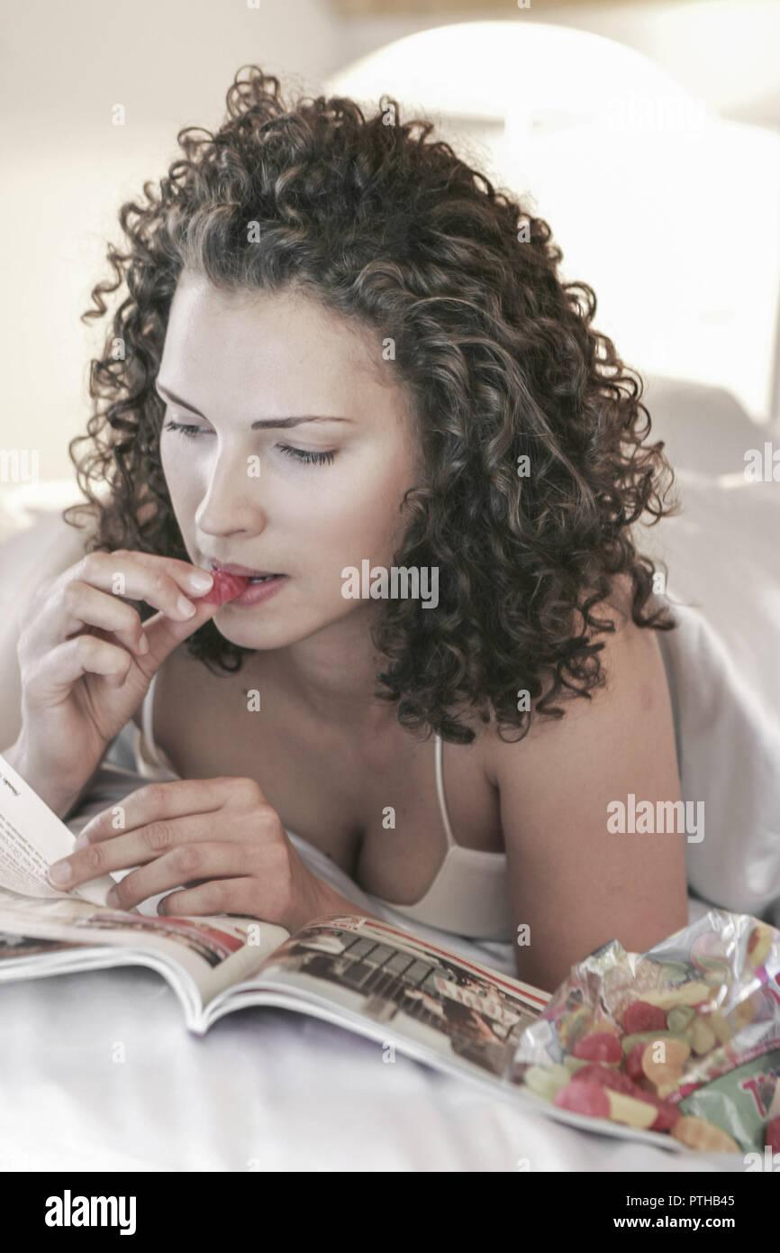 Frau Bett liegen Zeitschrift lesen Portrait blond langhaarig froehlich gluecklich entspannt Essen Naschen Suessigkeiten Fruchtgummi geniessen Lifestyl - Stock Image
