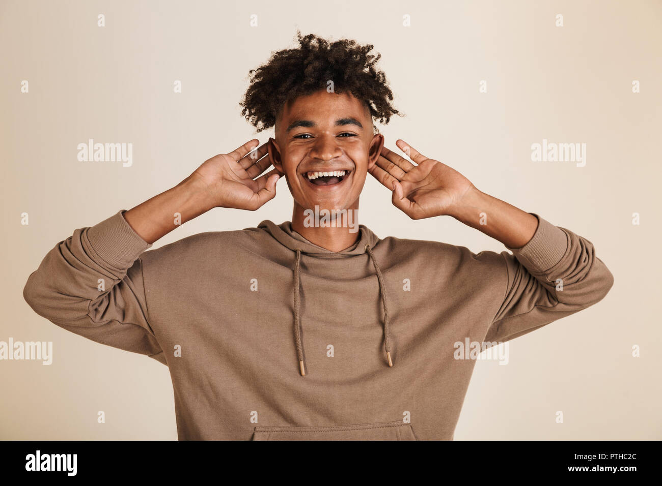 Portrait of a smiling young afro american man dressed in hoodie grimacing isolated - Stock Image