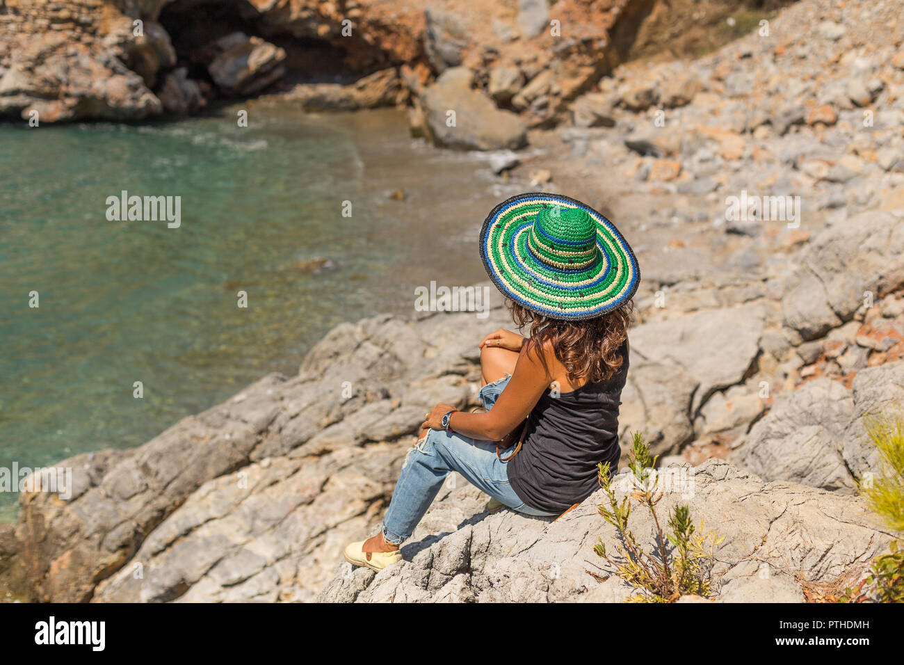 Backview portrait of a solo traveller female wearing green and blue striped hat, black t-shirt and jeans, sitting at the rocks looking at beautiful ba - Stock Image