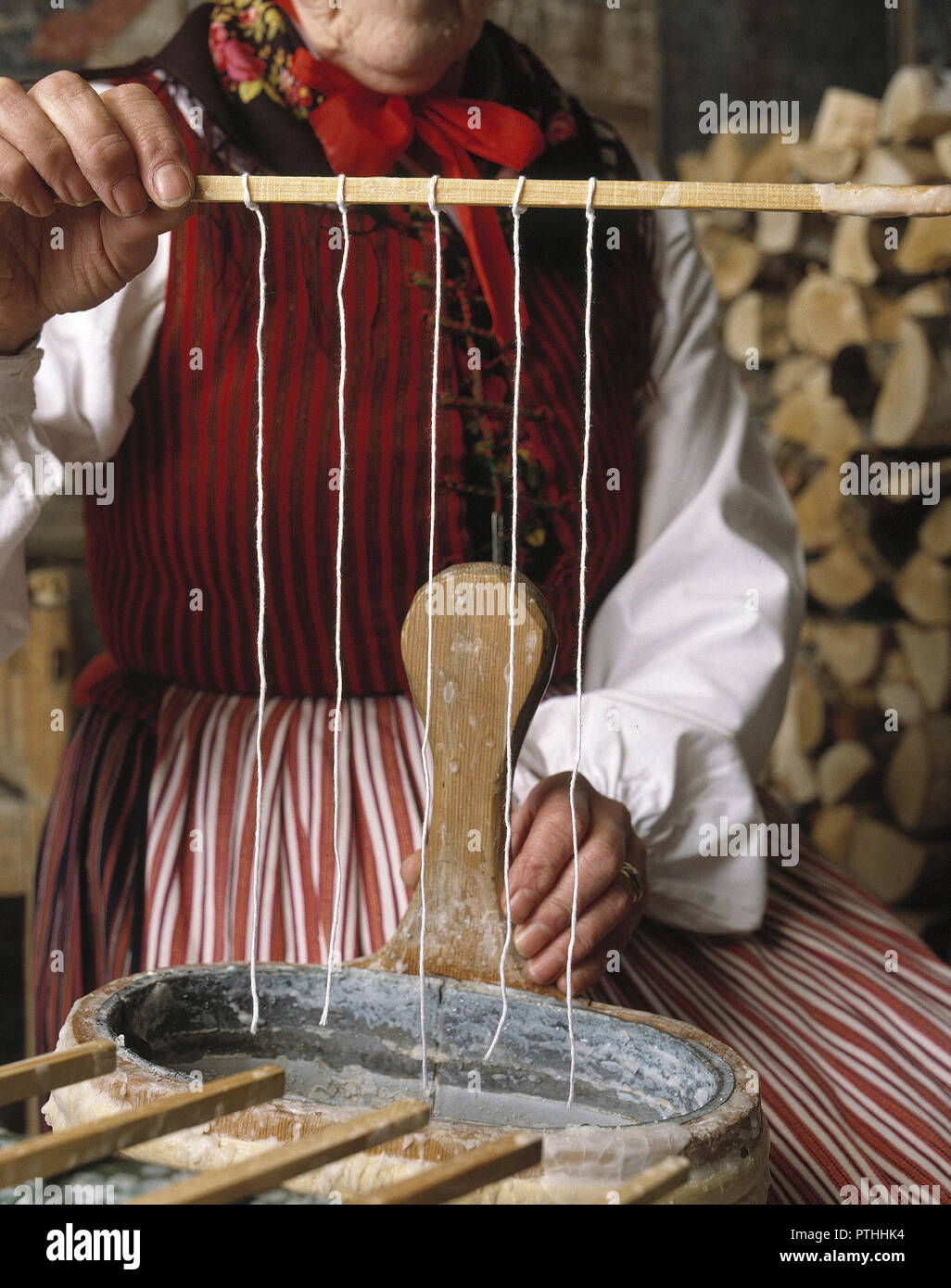 Making candles. A woman dressed in traditional Swedish folk costume are making candles. She dips the candlewicks into the liquid stearin many times, and add layer on layer of stearin onto the candel, until it's ready. - Stock Image