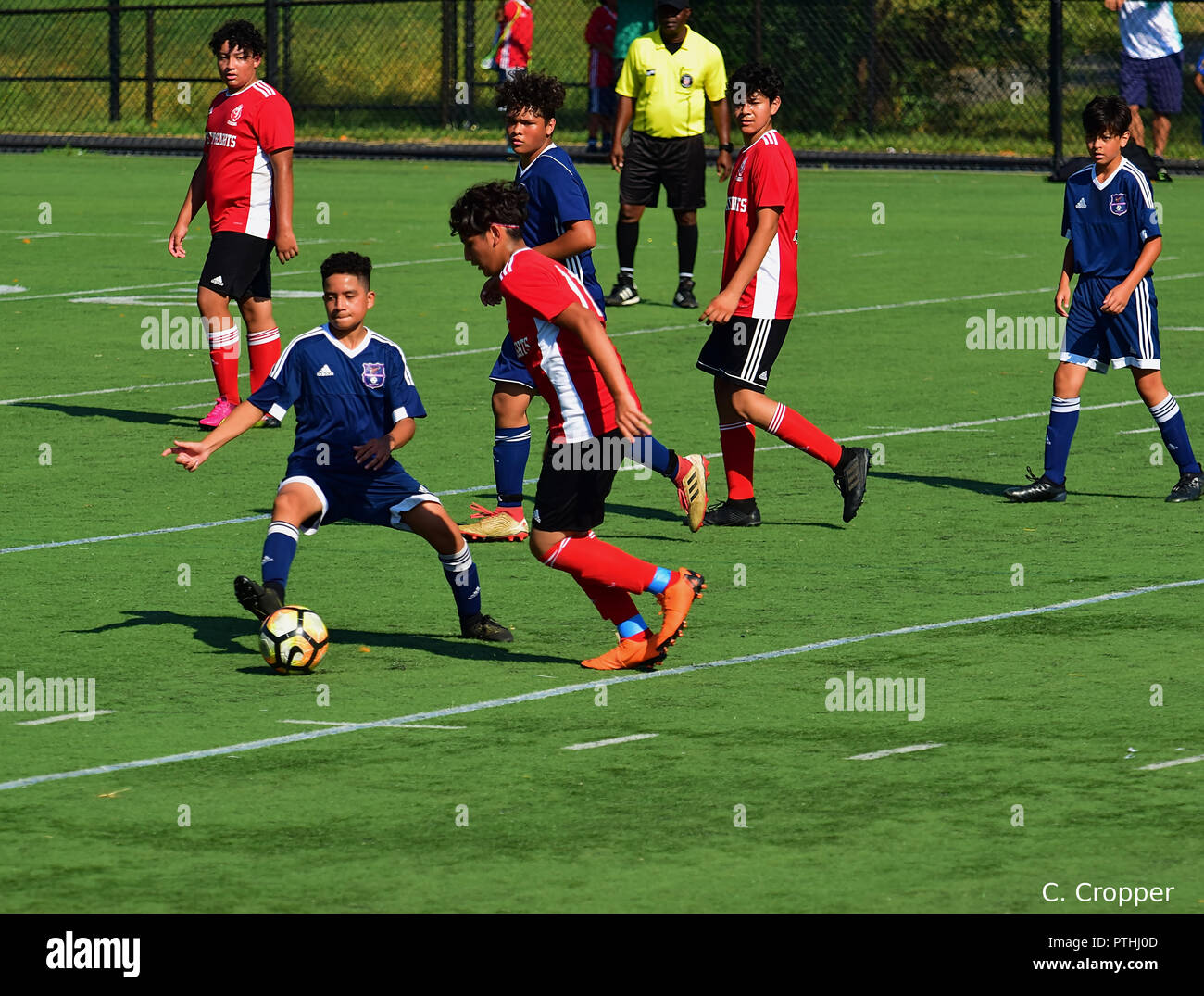 Youths playing organized soccer on field - Stock Image
