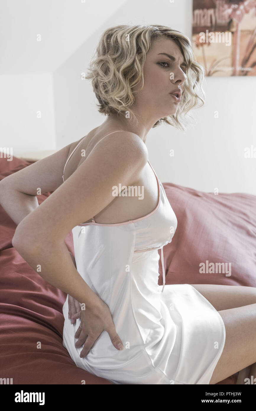 Frau, Nachthemd, schlaflos, am Morgen, Morgens, Gestik, , Seitenansicht, innen, Bett, sitzen, jung, abstuetzen, strecken, Schmerzen, Beschwerden, Kreu - Stock Image