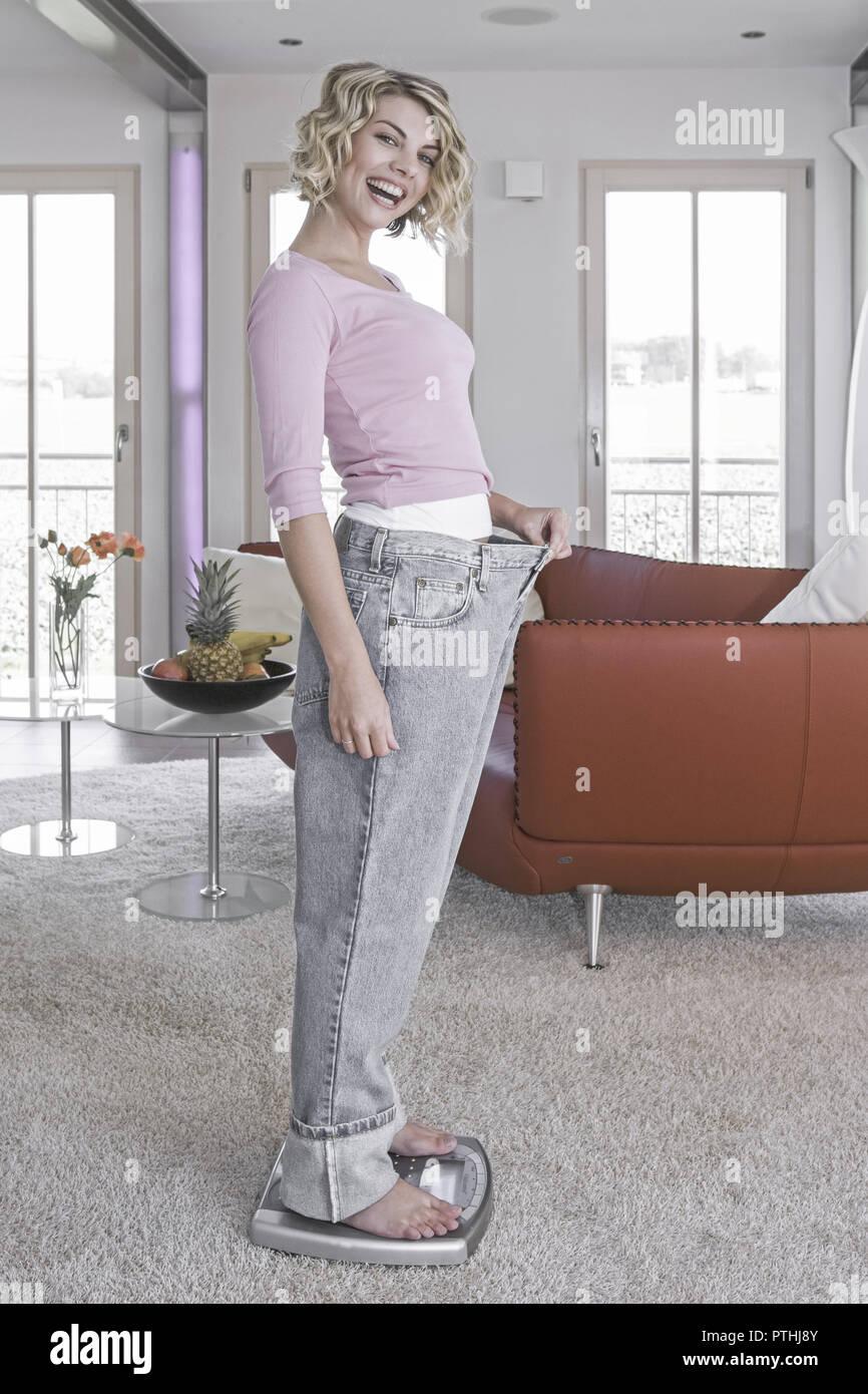 20-30 Jahre, Ausdruck, Bekleidung, Daumen, Diät, Frau, Freude, Gesichtsausdruck, Gestik, Gewicht, Glueck, Gluecksgefuehl, Hand, Hose, Jeans, zu gross, - Stock Image