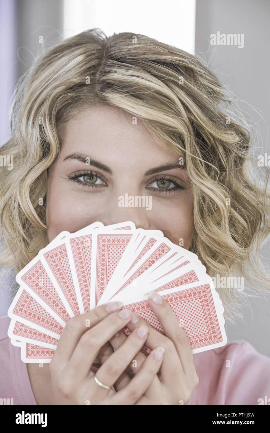 Frau, jung, junge, 20, 30 Jahre, Portrait, Karten, Kartenspiel, spielen, Spiekarten, Pokern, Pokerface, Pokergesicht, Freizeit, Spiel, Unterhaltung, G - Stock Image