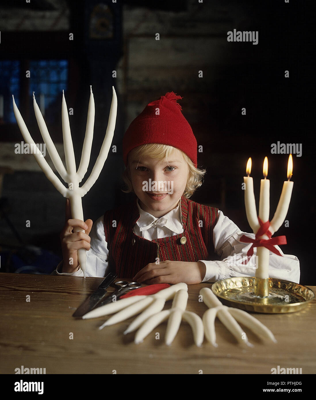 Making candles. A boy dressed in traditional Swedish folk costume holds a handmade stearin candle. They dip the candlewick into the liquid stearin many times, and add layer on layer of stearin onto the candel, until it's ready. This candle with five arms is an old swedish handcrafted candle tradition. - Stock Image