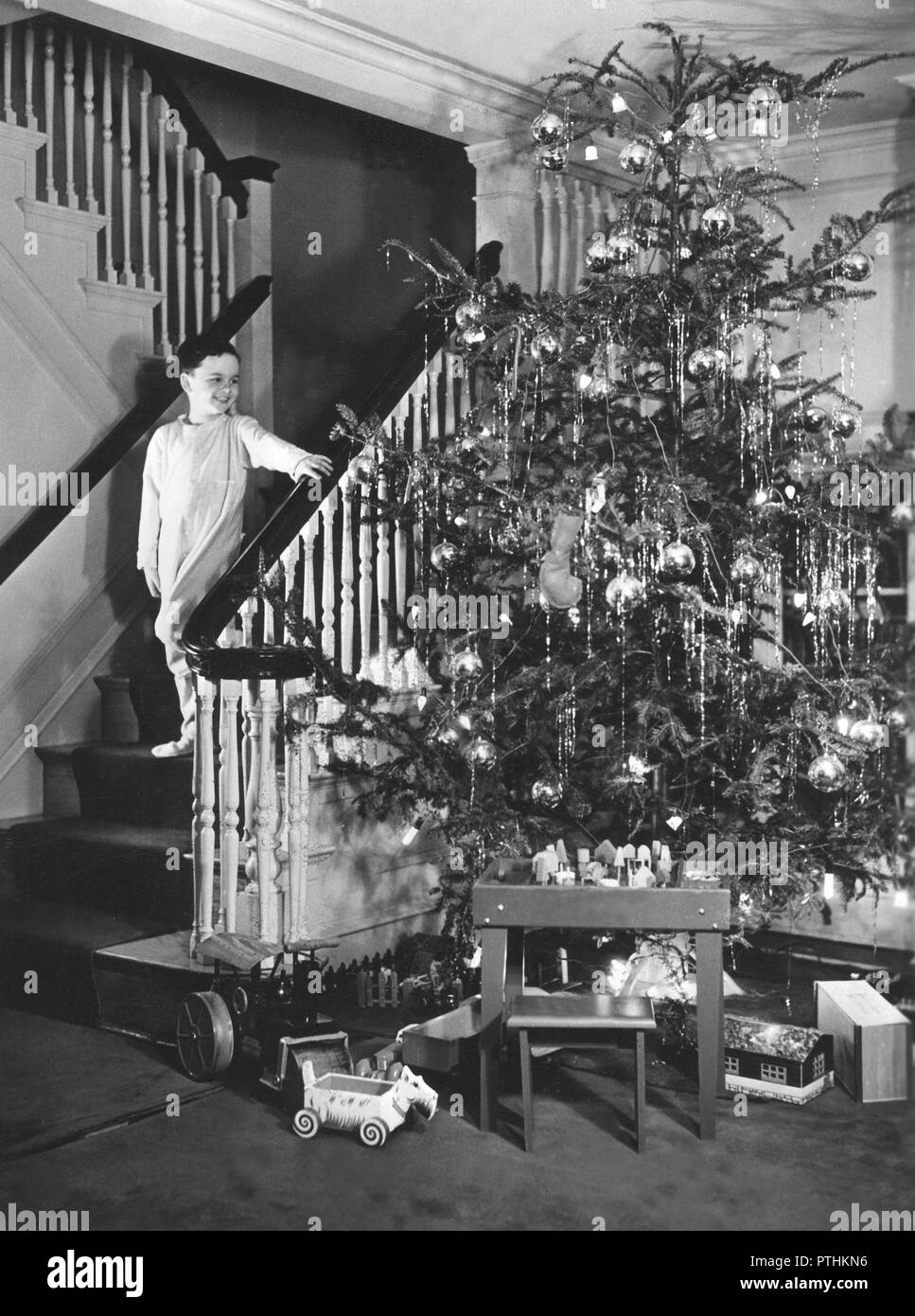 Christmas in the 1940s. A boy is coming down the stairs on christmas day, to the room where the christmas tree is standing. There are christmas presents under the tree. Sweden 1940s - Stock Image