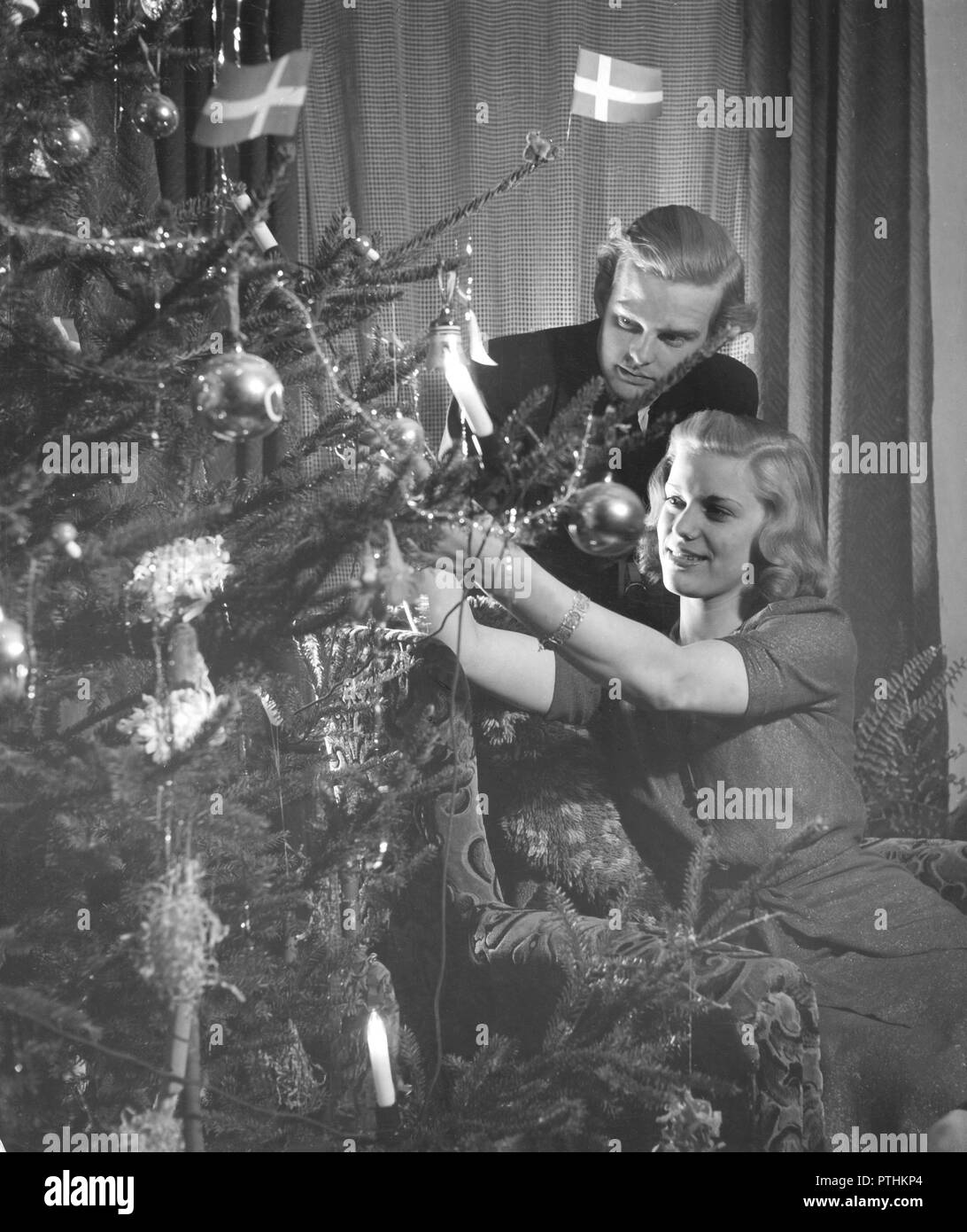 christmas in the 1940s a young couple is putting christmas decorations on the christmas tree sweden 1940s