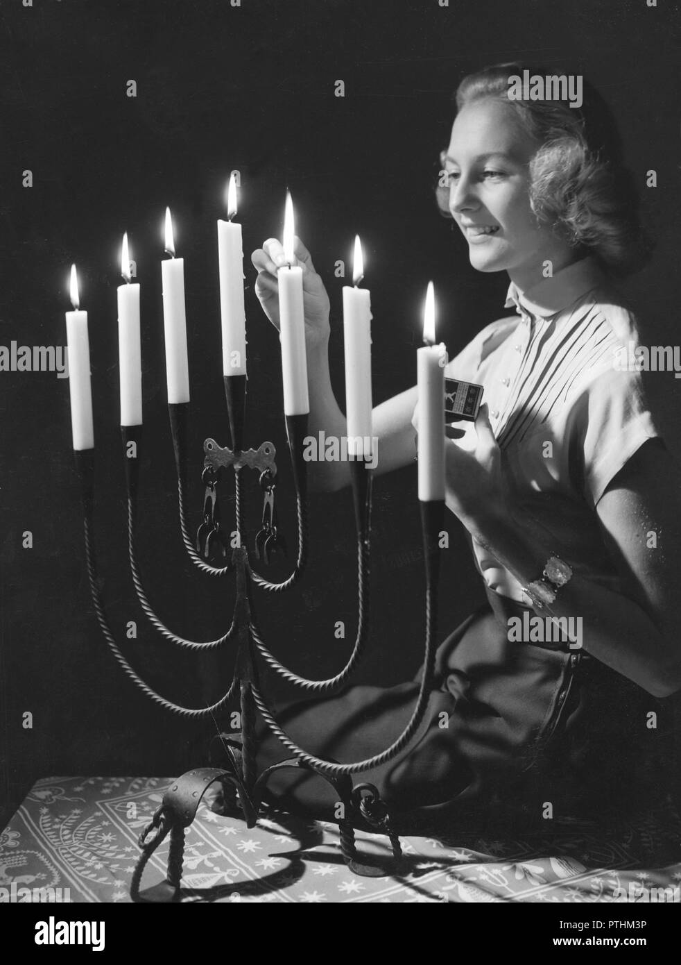 Christmas in the 1940s. Margit Sjödin is lighting the candles at christmas. Sweden 1940s - Stock Image