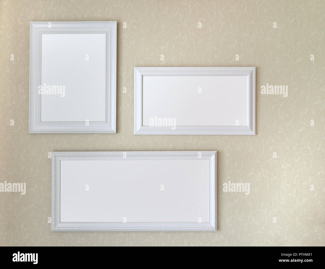 three white wooden frames hanging on soft yellow wall mock up