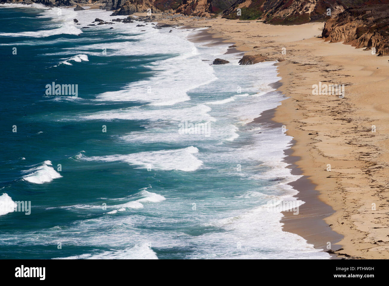 Pacific ocean waves roll in at The private beach below the Point Sur lighthouse along Highway 1 in Big Sur, California. Stock Photo