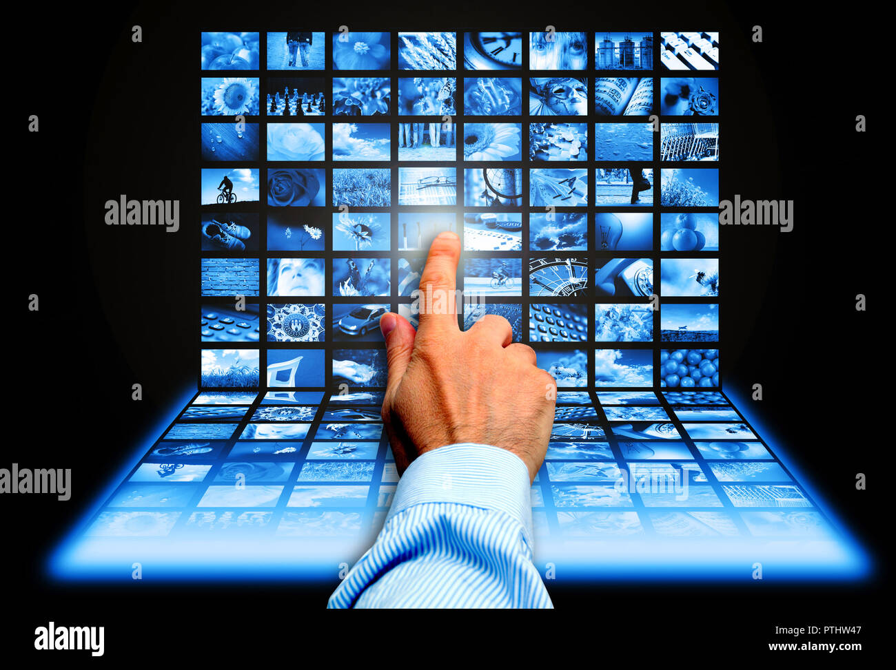 hand touching a screen with many technology images - Stock Image