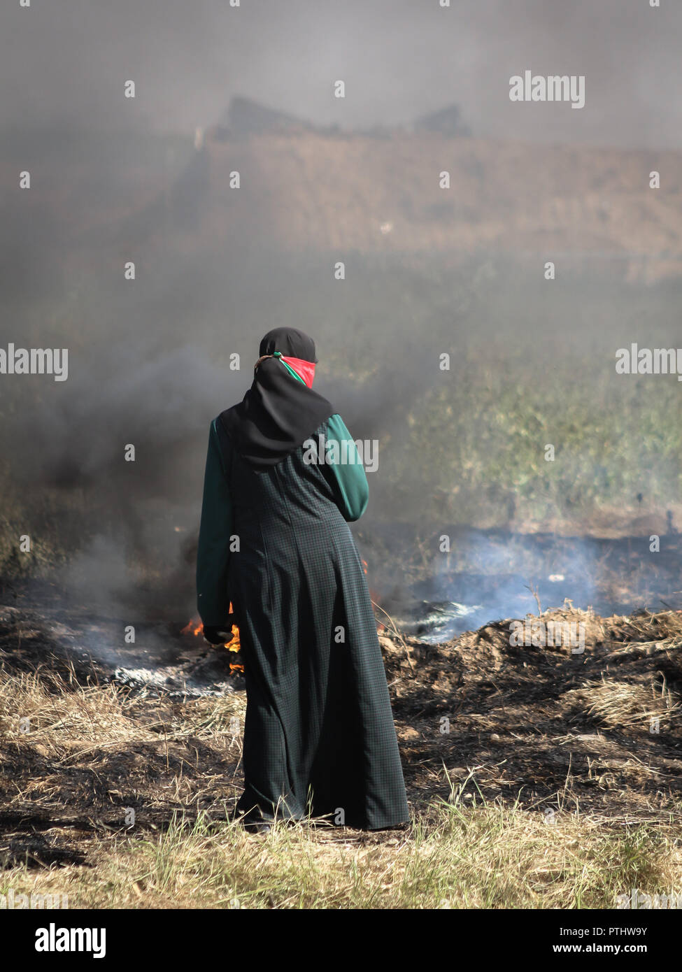 A Palestinian girl in front of Israeli soldiers on the Israel-Gaza border during a tent city protest demanding the right to return to their homeland. - Stock Image