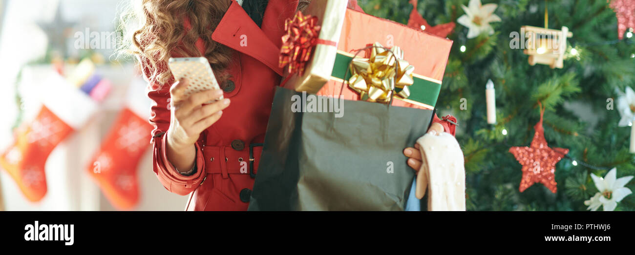 smiling trendy woman in red trench coat with shopping bag full of Christmas present boxes sending text message from phone near Christmas tree - Stock Image