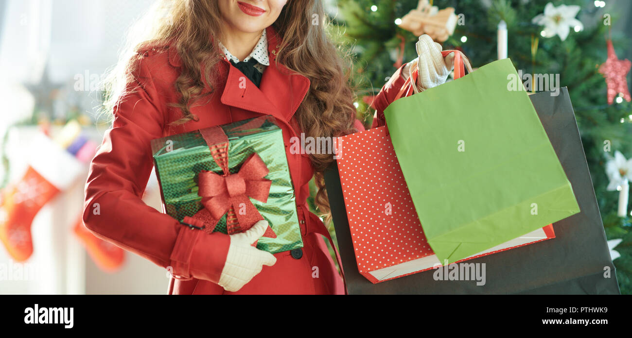 smiling trendy woman in red trench coat with shopping bags and Christmas present box near Christmas tree - Stock Image