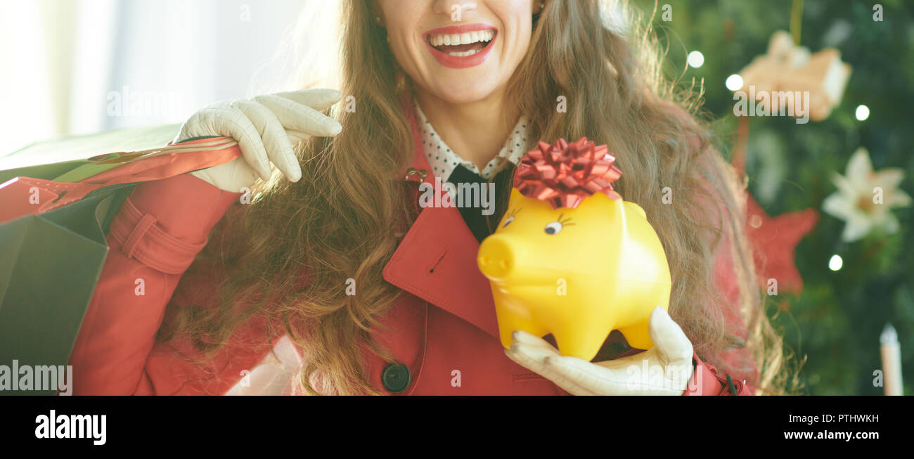 Closeup on happy young woman in red trench coat with shopping bags and yellow piggy bank near Christmas tree - Stock Image