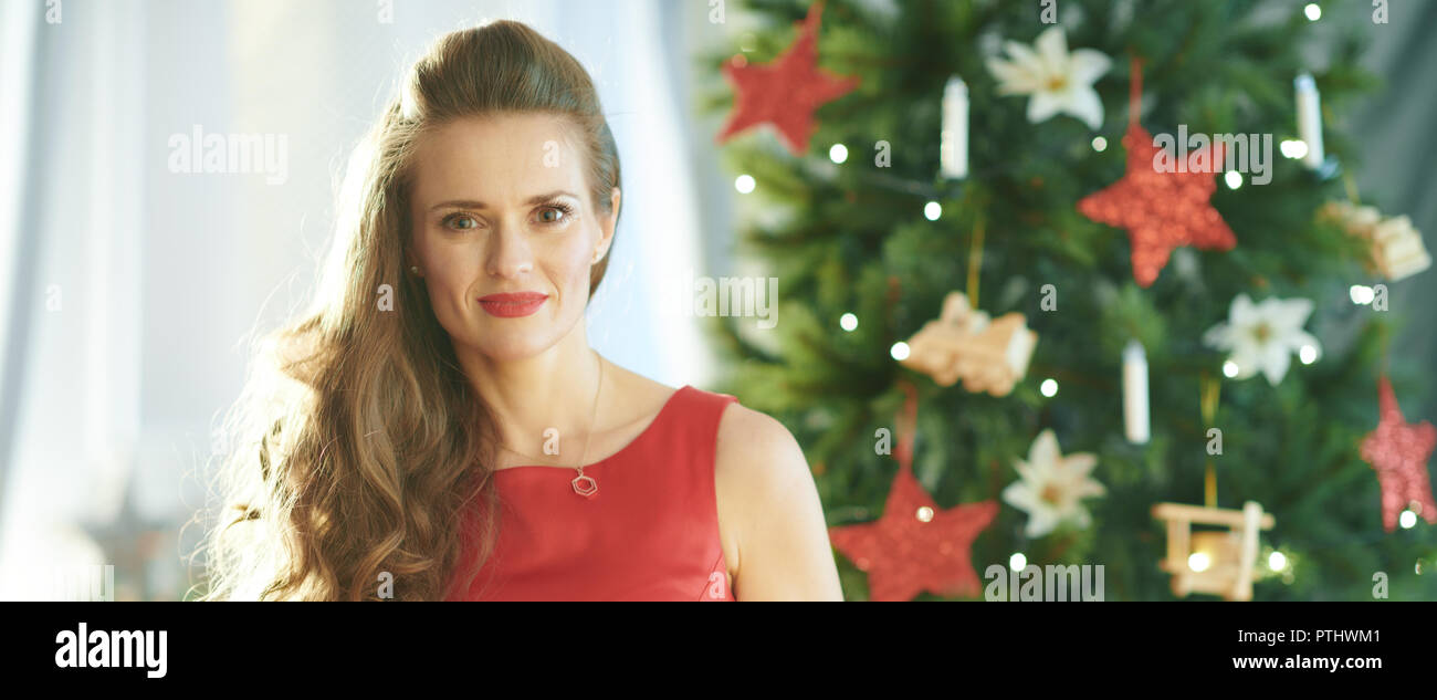young woman in red dress near Christmas tree - Stock Image