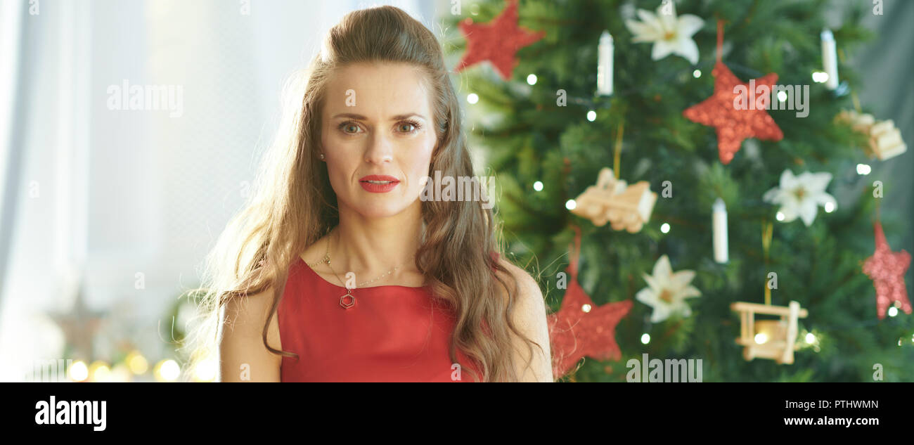 stylish woman in red dress near Christmas tree - Stock Image