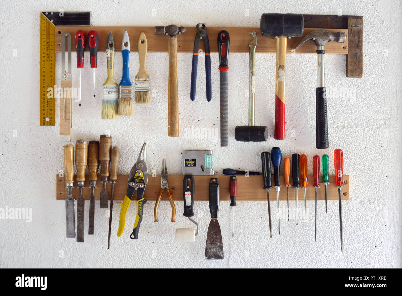 Woodworking Tools & Hand Tools including Screw Drivers, Paint Brushes and Hammers Hanging in Workshop or Garage Wall-Mounted Tool Rack - Stock Image