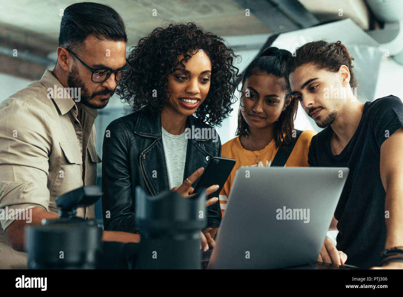 Photographer with his team looking at the photographs on a laptop. Model holding mobile phone standing with photographers looking at shoot photos. - Stock Image