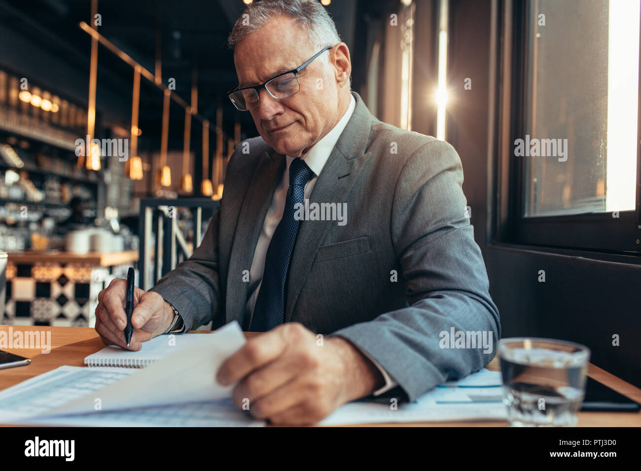 Senior businessman sitting at cafe table reading a document and making notes. Mature man in suit working on new project budget. - Stock Image