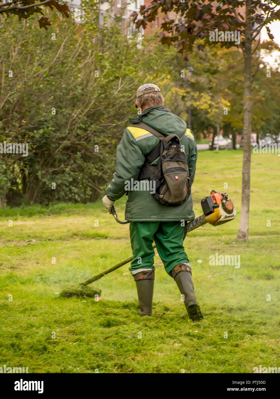 Workers mow the grass on the lawn in the city square. - Stock Image
