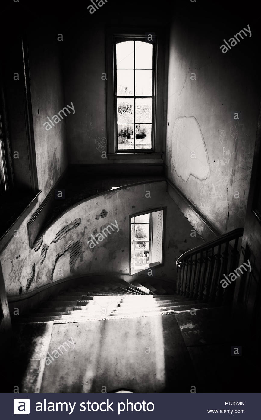 Left from a bygone era. Spiral staircase and light filtering in from two windows. - Stock Image