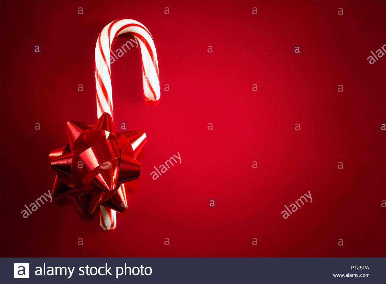 red foil bow and candy cane on red background for christmas themed