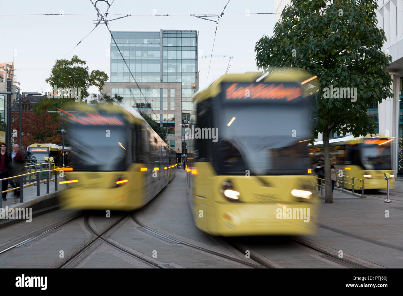 Three Metrolink trams depart St Peter's square stop in Manchester city centre, UK. - Stock Image