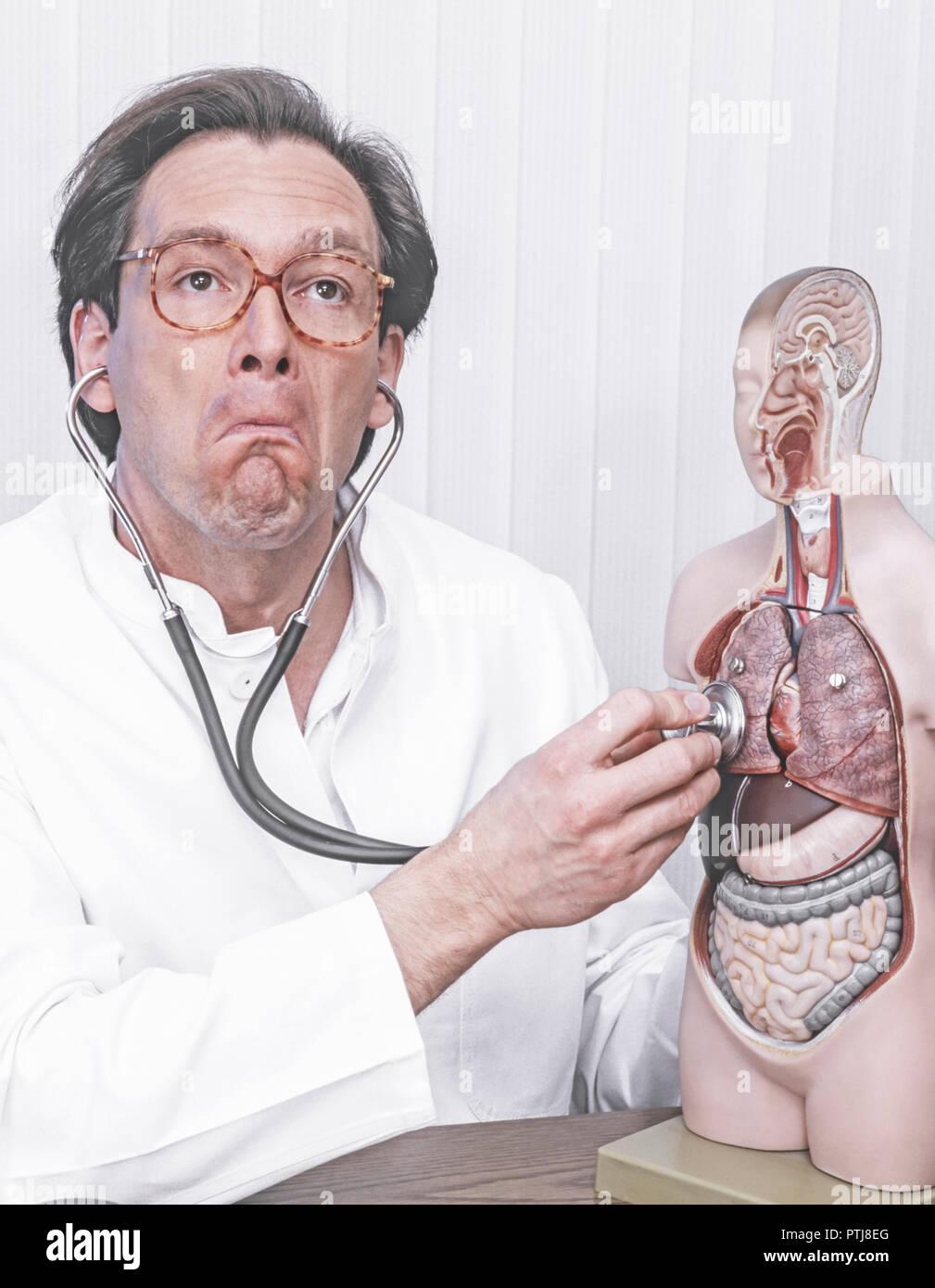 Arzt hoert mit dem Stethoskop an einem Modell Mimik (Modellfreigabe) Stock Photo