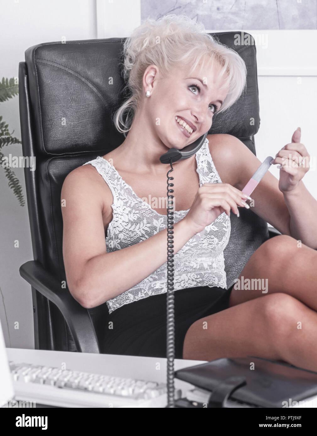 Sekretaerin feilt ihre Fingernaegel im Buero und telefoniert dabei (Modellfreigabe) - Stock Image