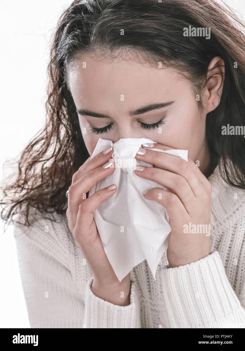 Erkaeltete junge Frau schnaeuzt in ein Papiertaschentuch (Modellfreigabe) Stock Photo
