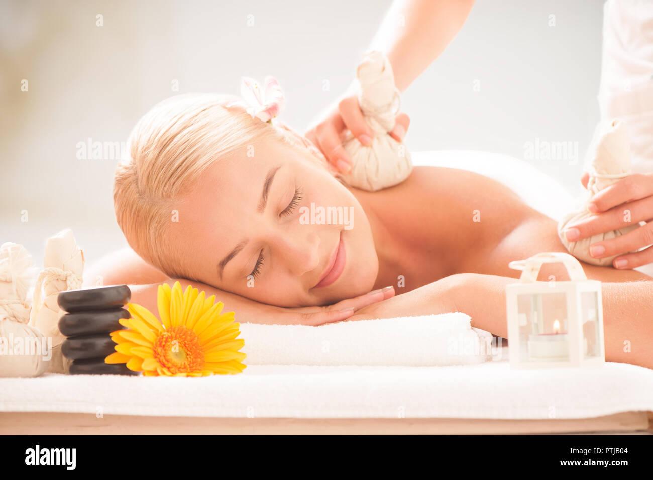 Blonde lady enjoying massages at health spa - Stock Image