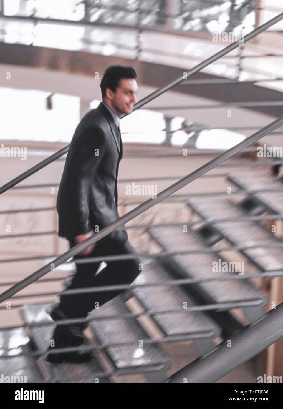 Karrieremann in Anzug mit Aktenkoffer laeuft eine Treppe hinauf (Modellfreigabe) Stock Photo