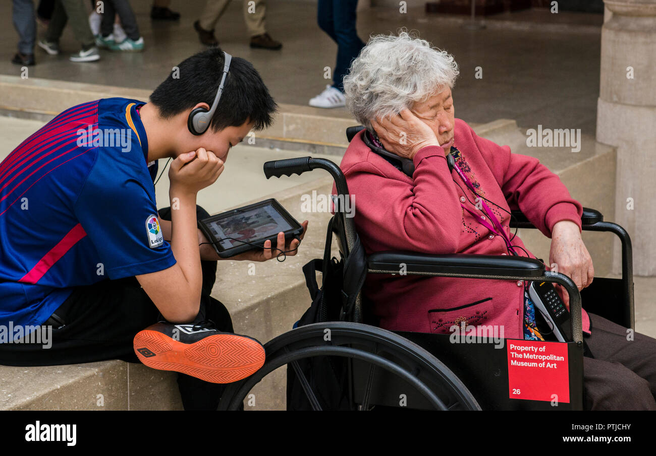 A boy is watching a film on his tablet next to a lady asleep in her wheelchair in the main hall of the Metropolitan Museum. - Stock Image