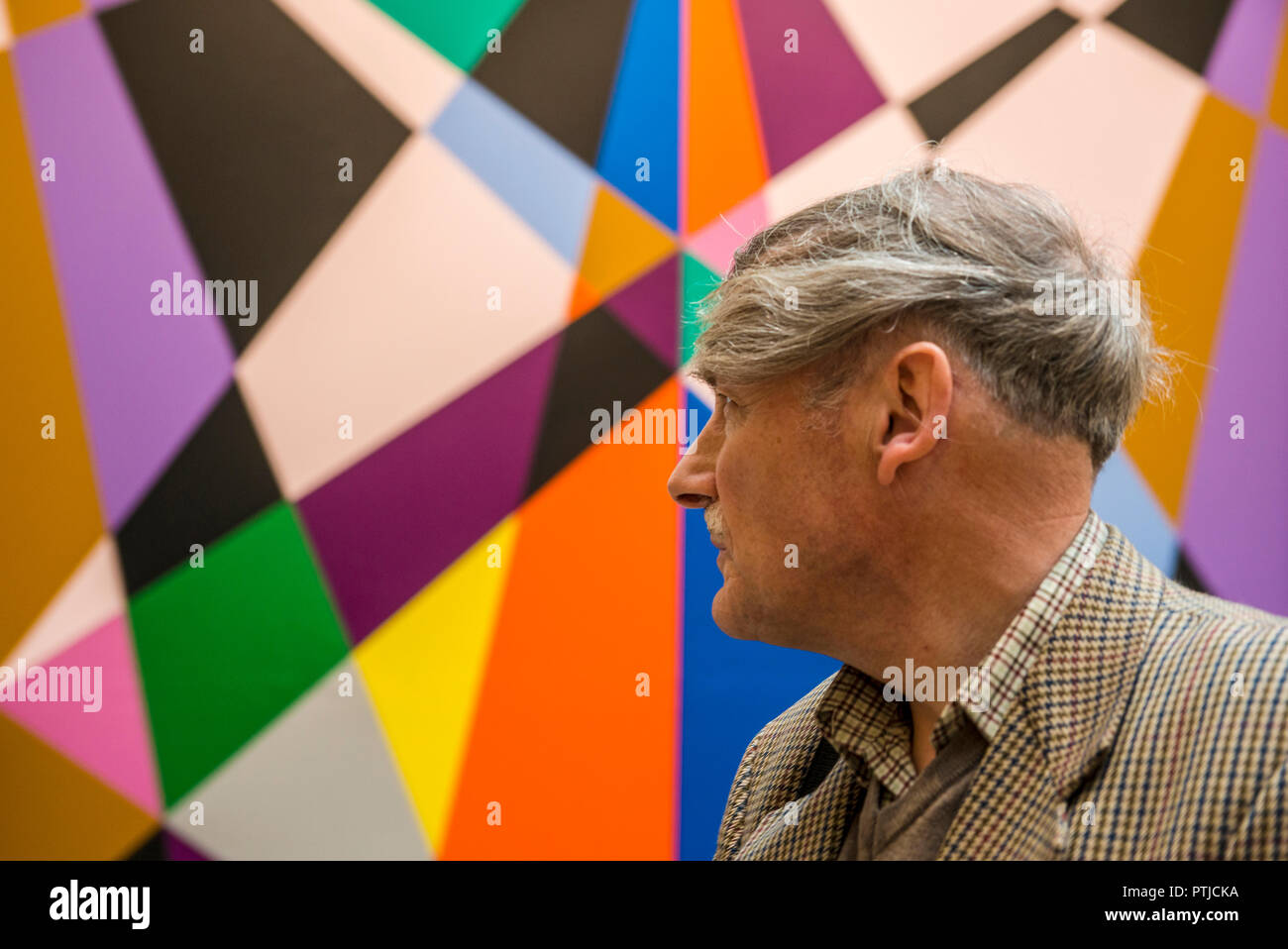 Man looking towards brightly coloured geometric artwork in the Modern Art Gallery in Leeds. - Stock Image