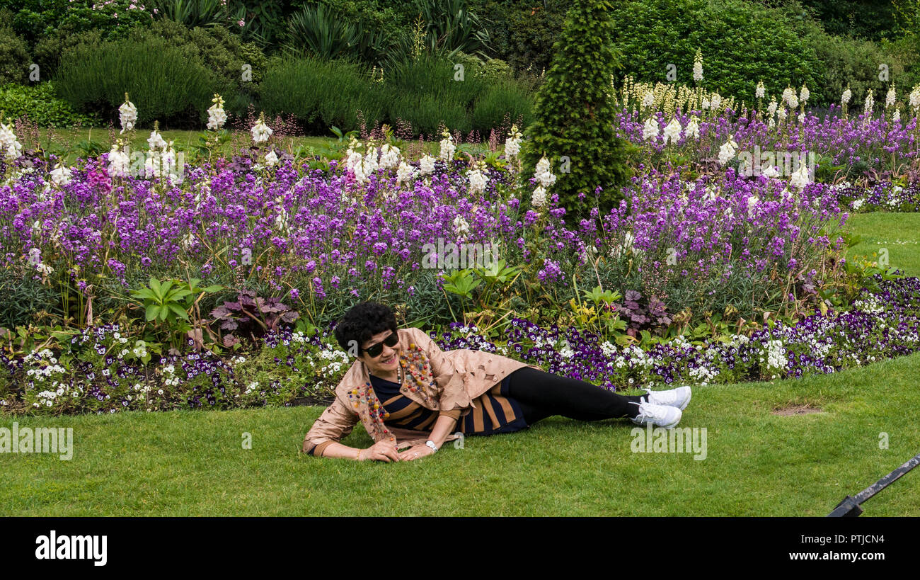 A Japanese lady enjoying the weather in Hyde Park resting on the grass in front of colourful flowers and wearing a floral patterned jacket. - Stock Image