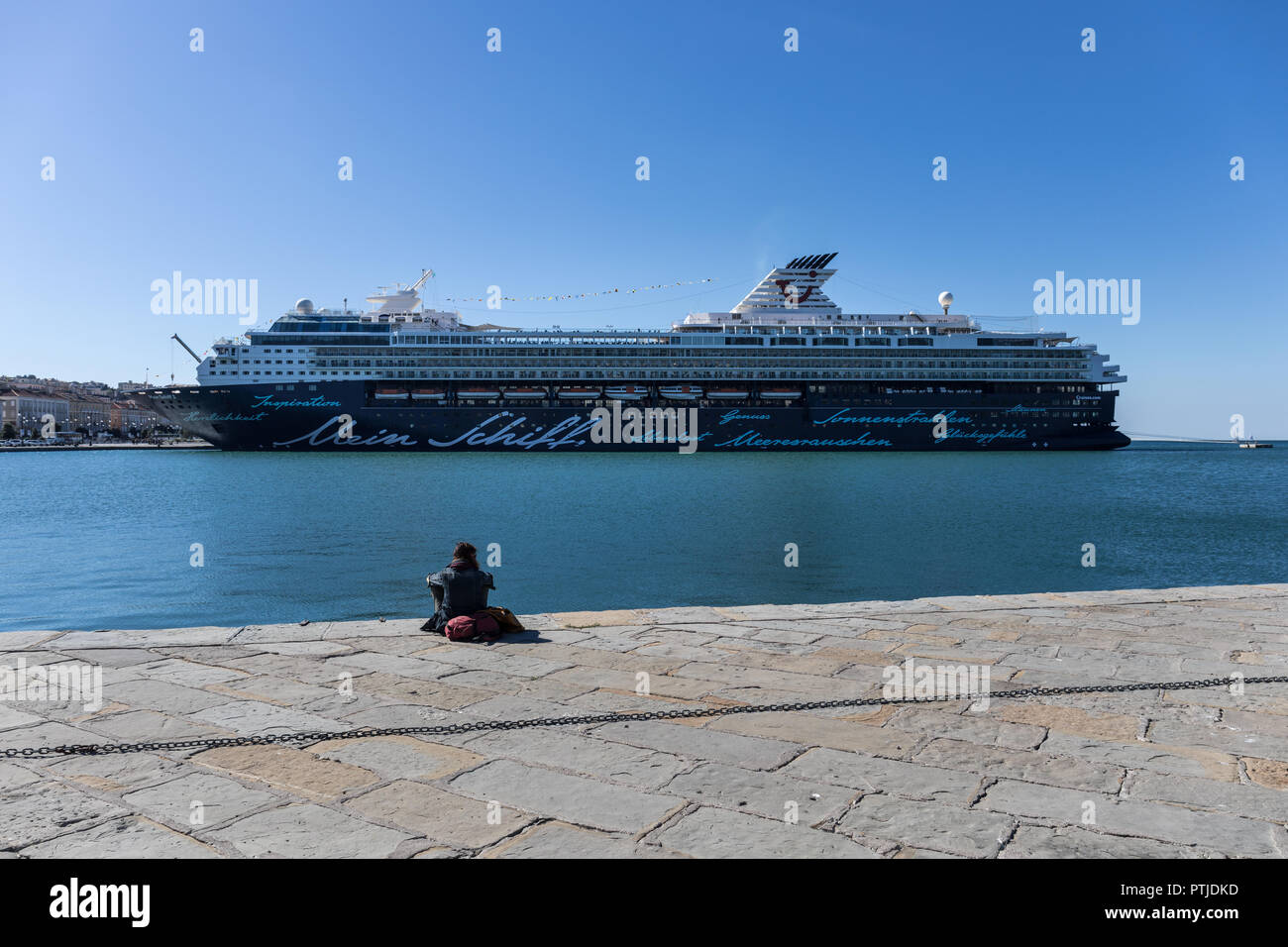 Woman sitting on the Audace pier (Molo Audace) watching a luxury cruise ship Mein Schiff 2 docked in the port of Trieste, Friuli Venezia Giulia, Italy - Stock Image