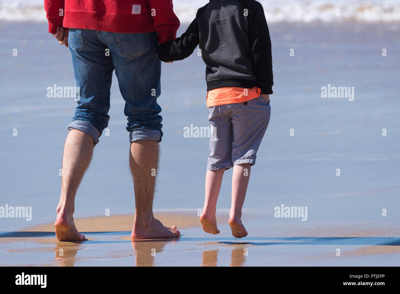 A father and his excited son standing on Fistral Beach in Newquay in Cornwall. - Stock Image
