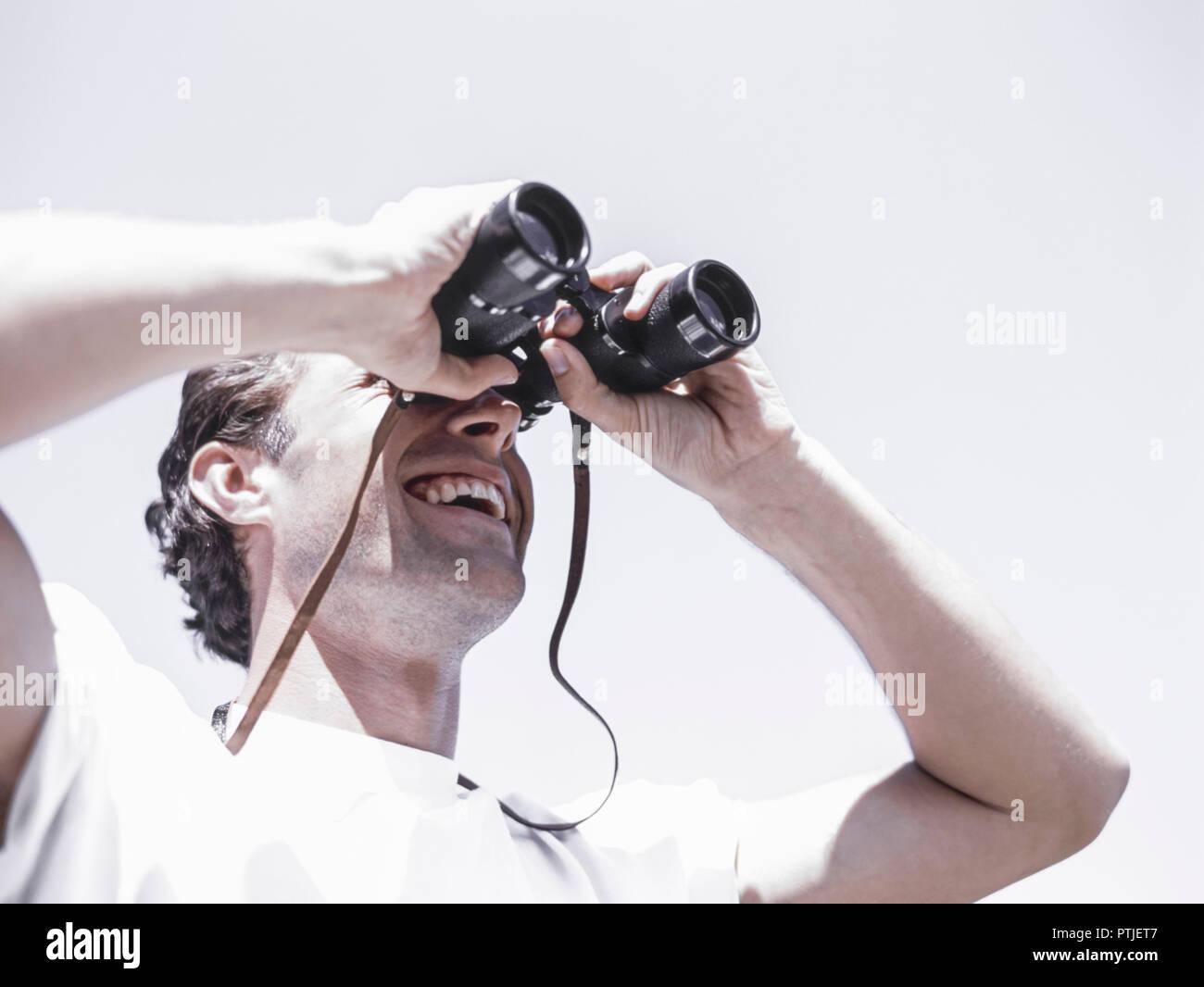 Mann beim wandern blickt durch ein fernglas modellfreigabe stock