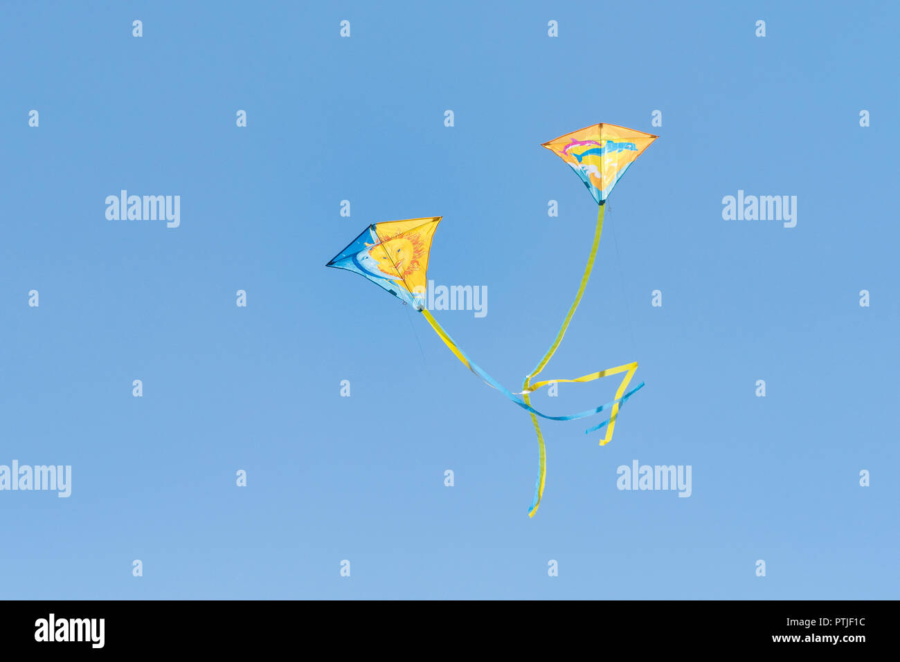 Two colourful kites flying against a cloudless blue sky. - Stock Image