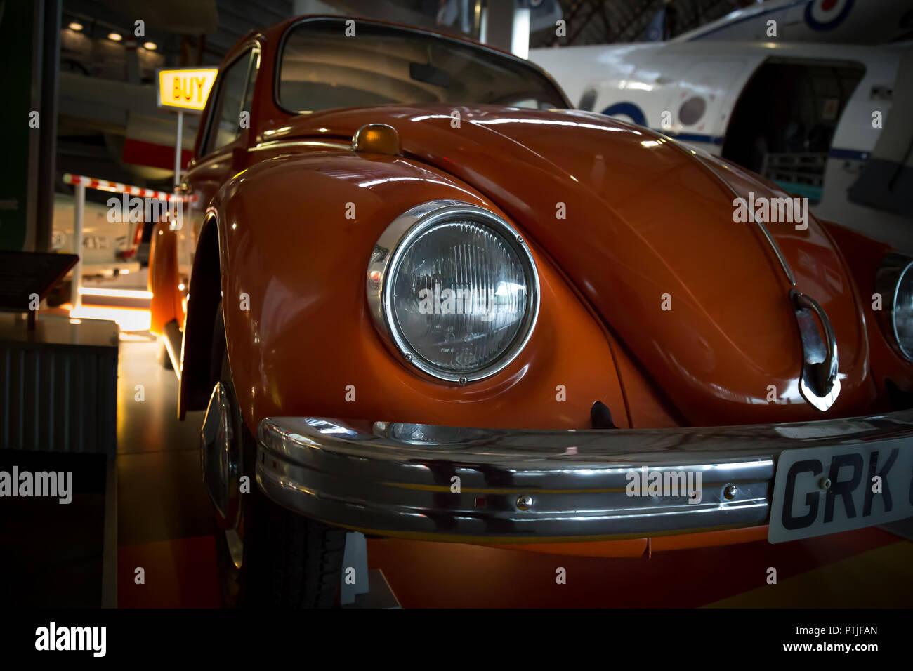 Arty, low-angle, landscape close up of burnt orange coloured Volkswagen Beetle, from the front. Car is stationary inside exhibition hall. - Stock Image