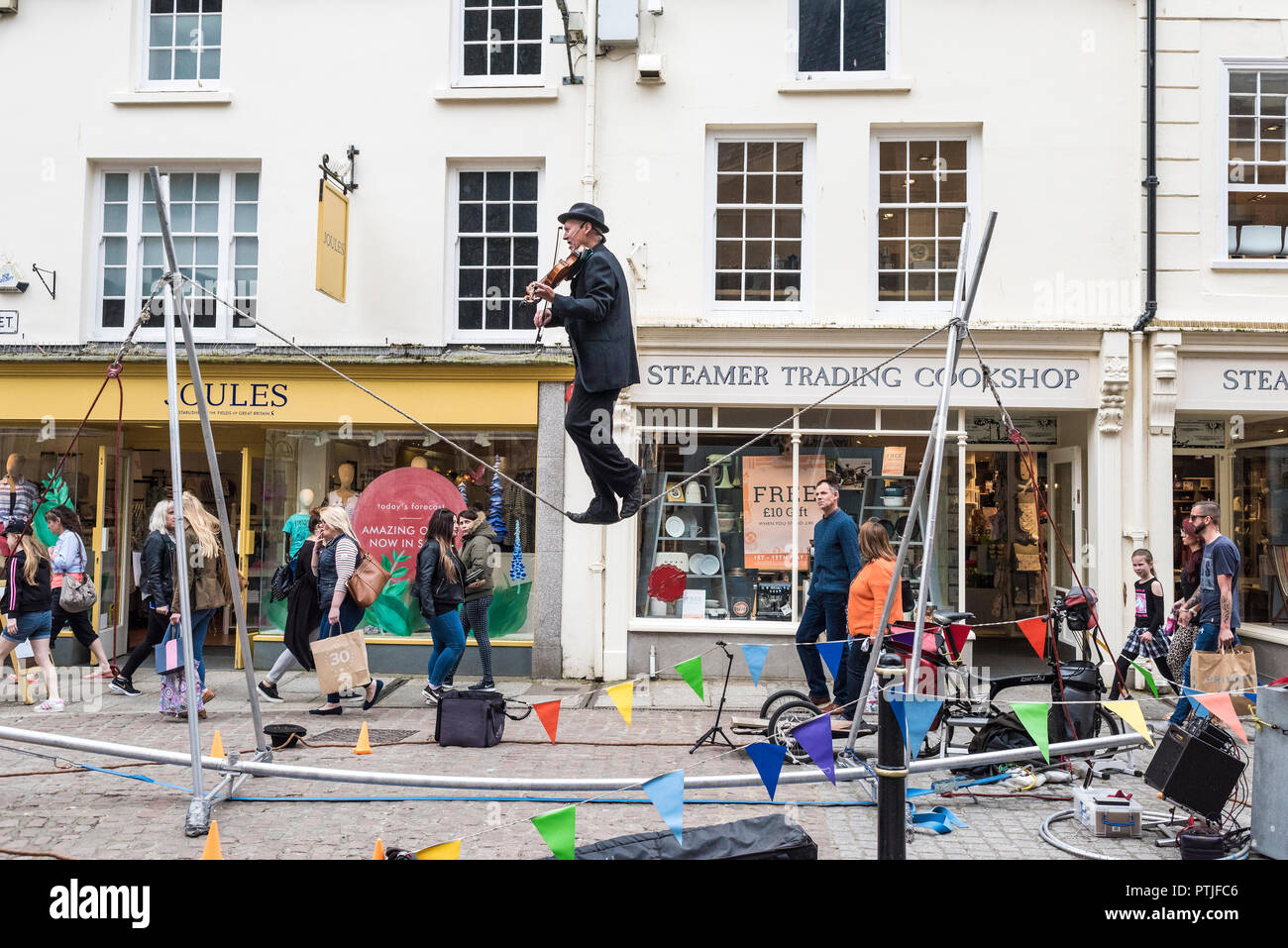 A street entertainer playing the violin and balancing on a slack line in Truro City centre in Cornwall. - Stock Image