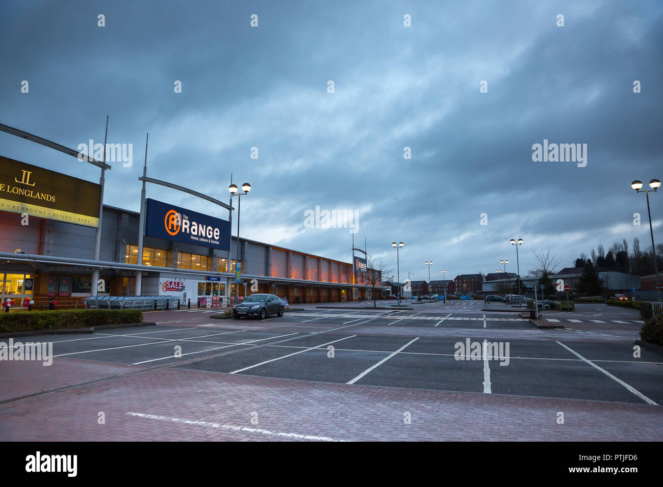 Early morning, landscape shot of the empty car park at a UK retail park - all before the shoppers arrive for the January sales. Winter morning. - Stock Image